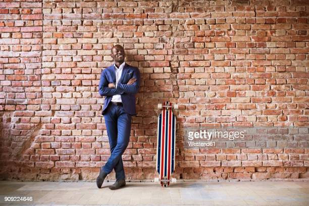 smiling businessman with longboard at brick wall - black suit stock pictures, royalty-free photos & images