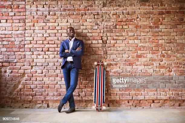 smiling businessman with longboard at brick wall - lehnend stock-fotos und bilder
