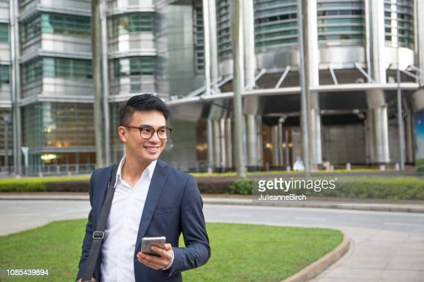 smiling businessman with mobile phone looking away - handsome chinese men stock pictures, royalty-free photos & images