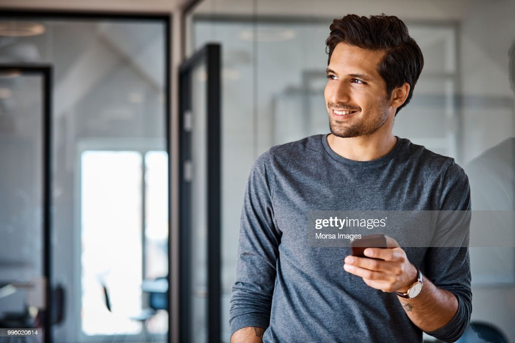 Smiling businessman with mobile phone looking away : Stock Photo