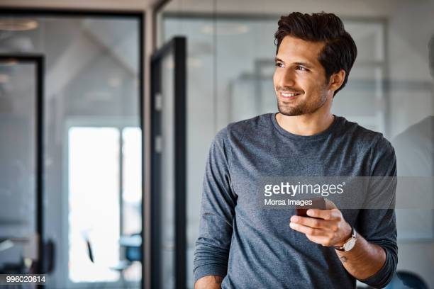 smiling businessman with mobile phone looking away - wegkijken stockfoto's en -beelden