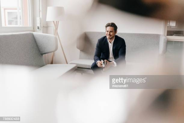 smiling businessman with notebook on couch - variable schärfentiefe stock-fotos und bilder