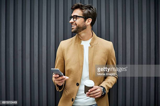 smiling businessman with smart phone and cup - elegantie stockfoto's en -beelden