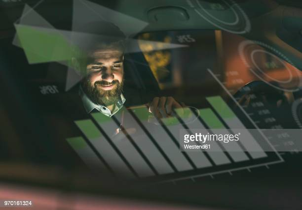 Smiling businessman with smartphone in car at night surrounded by data