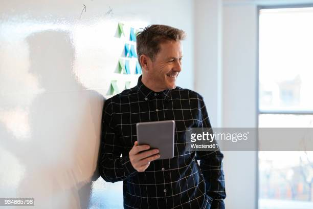 smiling businessman with tablet in office leaning against whiteboard - seitenblick stock-fotos und bilder