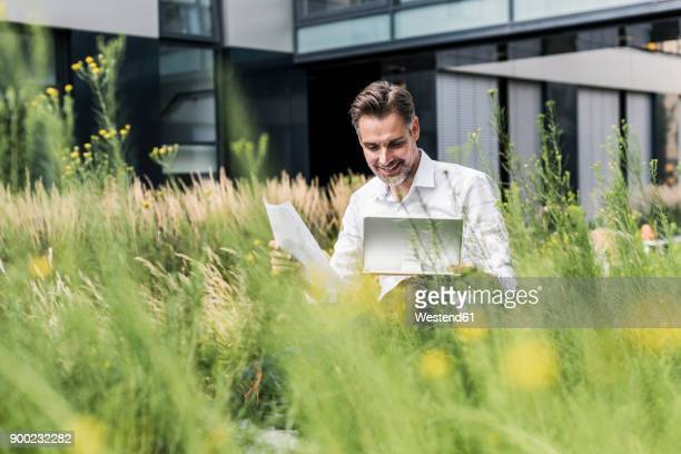 Smiling businessman working in grass outside office building