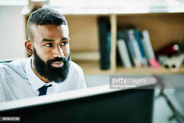 smiling businessman working on computer at office workstation - selective focus photos et images de collection