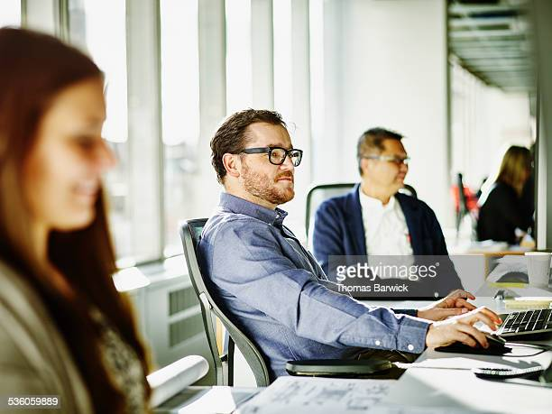 Smiling businessman working on project on computer