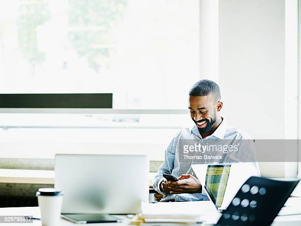 Smiling businessman working on smartphone
