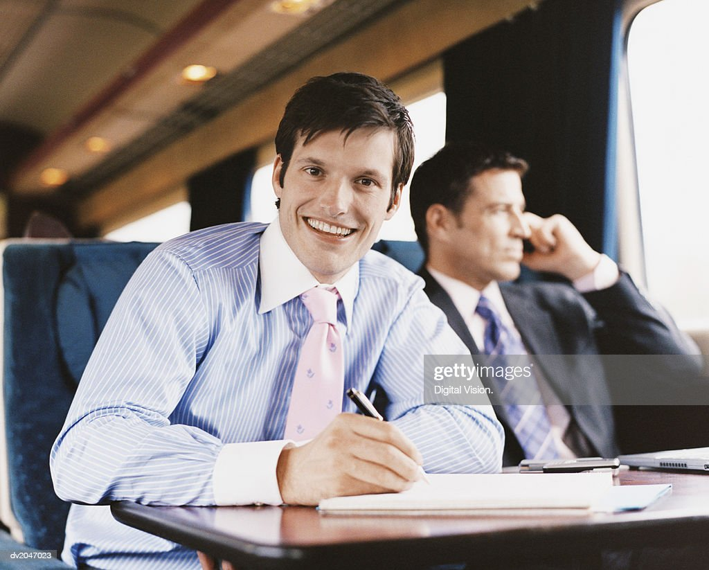 Smiling Businessman Writing in a Document on a Passenger Train : Stock Photo