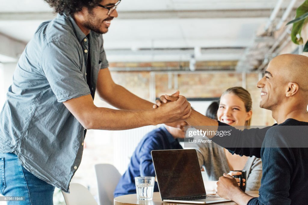 Smiling businessmen holding hands by colleagues at table : Stock Photo