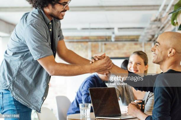 Smiling businessmen holding hands by colleagues at table