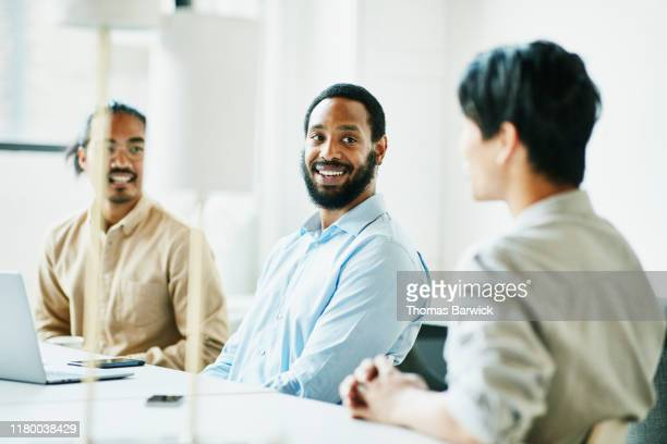 smiling businessmen in discussion during meeting in coworking office - diversity stock pictures, royalty-free photos & images