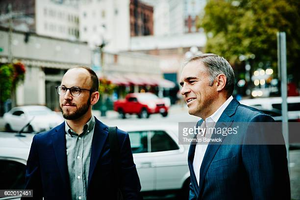 Smiling businessmen in discussion on sidewalk