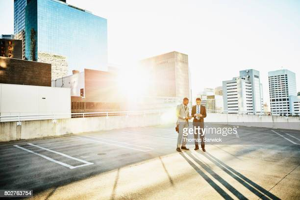 Smiling businessmen looking at smartphone at sunrise on downtown parking garage roof