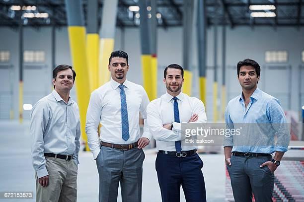 smiling businessmen posing in empty warehouse - 4人 ストックフォトと画像