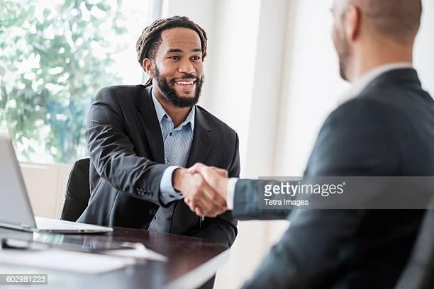 smiling businessmen shaking hands in office - dar cartas imagens e fotografias de stock