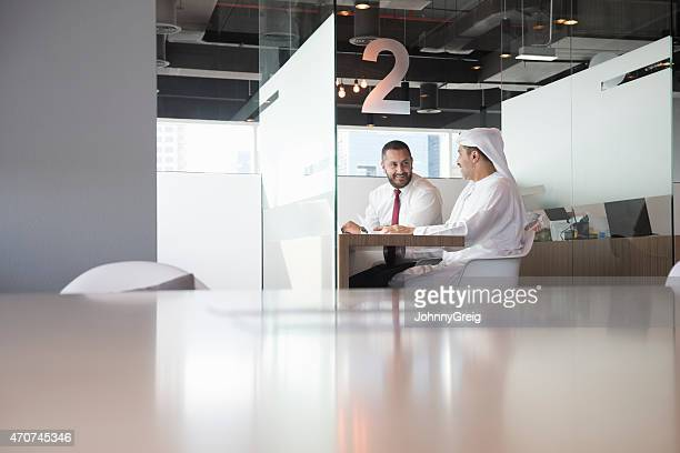 smiling businessmen sitting at desk in office - focus on background stock pictures, royalty-free photos & images