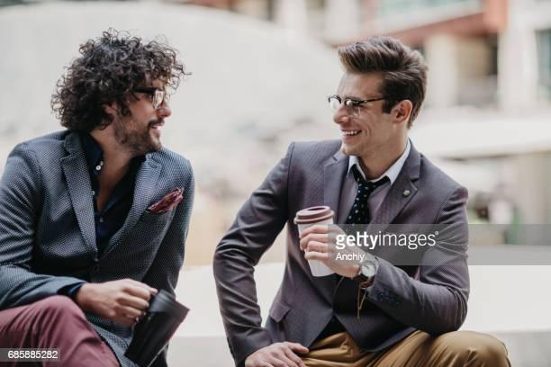 Lächelnde Geschäftsleute sitzen auf der Bank und trinken Kaffee