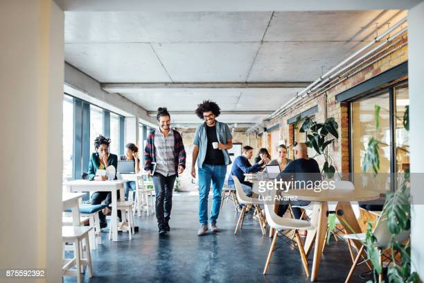 Smiling businessmen walking amidst colleagues at cafeteria