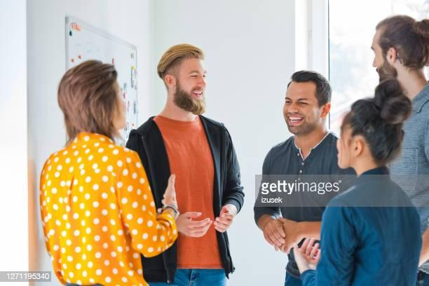 glimlachende zakenlieden met collega's in nieuw bureau - izusek stockfoto's en -beelden