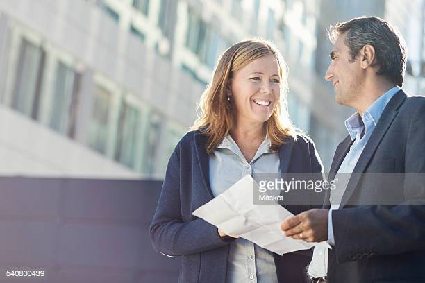 Smiling businesspeople discussing over document outside office building