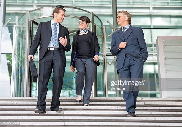 Comerciante sorridente a caminhar para baixo as escadas e comunicação