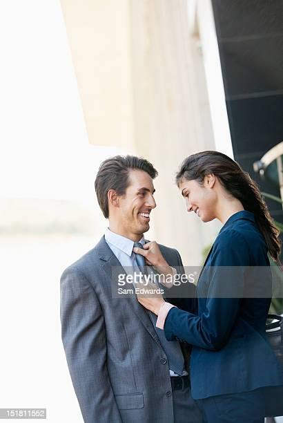 Smiling businesswoman adjusting businessmans tie