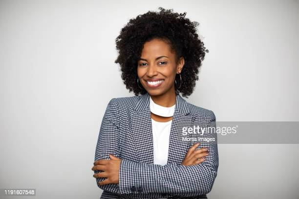 smiling businesswoman against white background - veste noire photos et images de collection