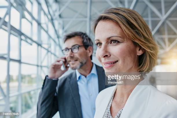 Smiling businesswoman and businessman on cell phone at the airport