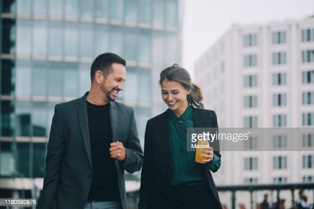 smiling businesswoman and businessman talking while walking in city - gemeinsam gehen stock-fotos und bilder