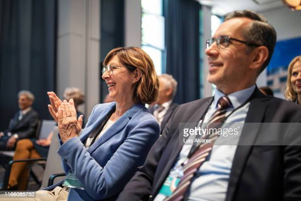 smiling businesswoman applauding during seminar - teilnehmen stock-fotos und bilder