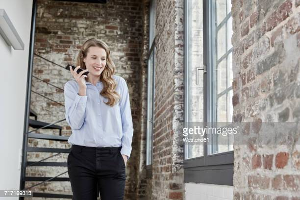 Smiling businesswoman at brick wall using cell phone