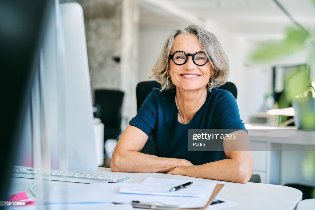Smiling businesswoman at desk in office : Stock Photo