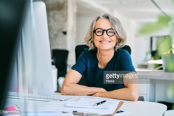 smiling businesswoman at desk in office - businesswoman stock pictures, royalty-free photos & images