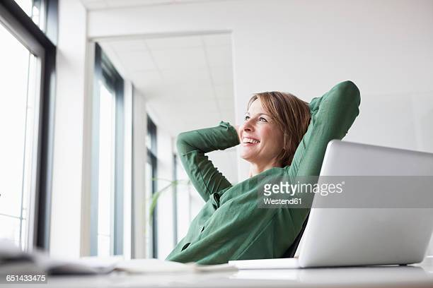 smiling businesswoman at office desk leaning back - hands behind head stock pictures, royalty-free photos & images