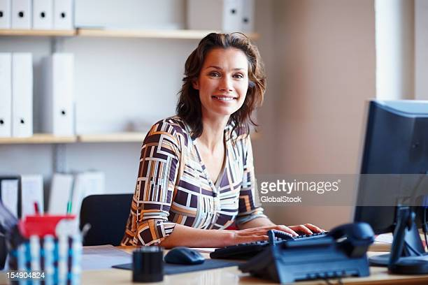 smiling businesswoman at office desk with a computer - administrator stock pictures, royalty-free photos & images