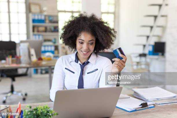 Smiling businesswoman at office shopping with credit card