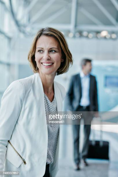 Smiling businesswoman at the airport looking sideways