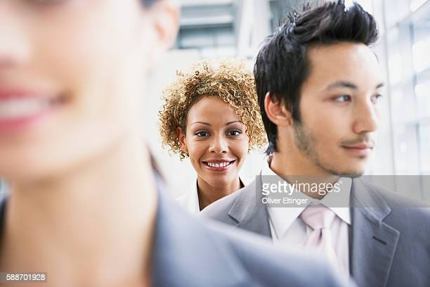 Smiling businesswoman behind businessman