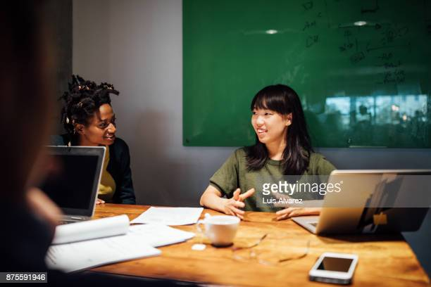 Smiling businesswoman discussing with colleague