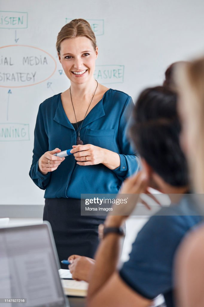Smiling businesswoman discussing with colleagues : Stock Photo