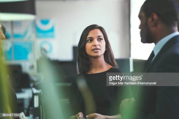 smiling businesswoman discussing with coworkers - serious stock pictures, royalty-free photos & images