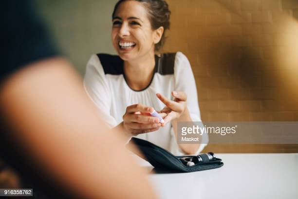 Smiling businesswoman doing blood sugar test while sitting with colleague at table in office