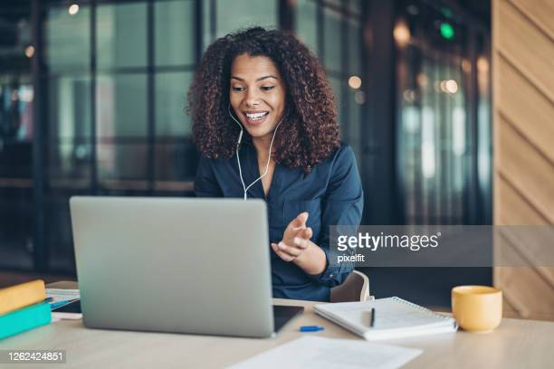 smiling businesswoman during a video call in the office - web conference stock pictures, royalty-free photos & images