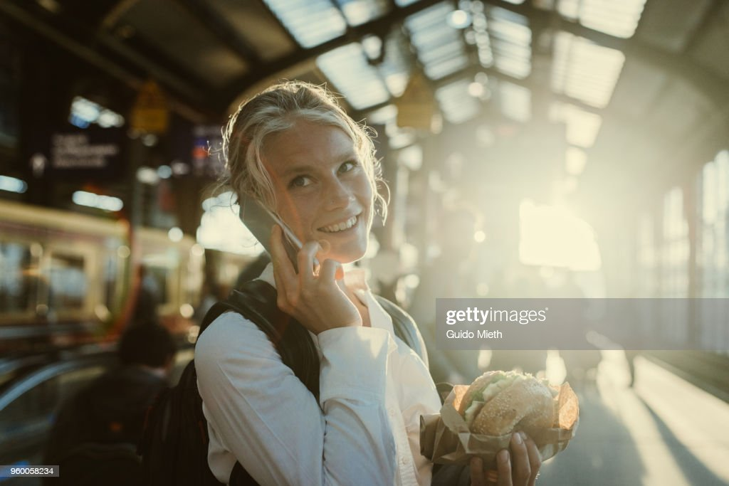 Smiling businesswoman eating a bagel. : Stock-Foto