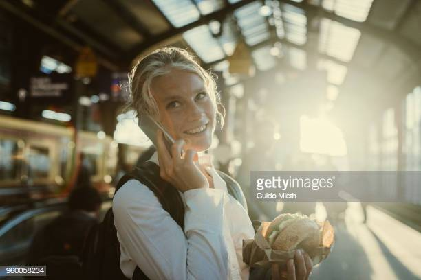 smiling businesswoman eating a bagel. - ungestellt stock-fotos und bilder
