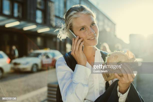 Smiling businesswoman eating a bagel.