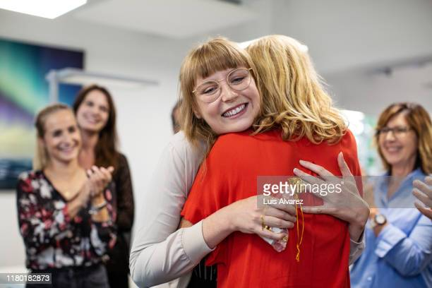 smiling businesswoman embracing colleague in office - ladder of success stock pictures, royalty-free photos & images