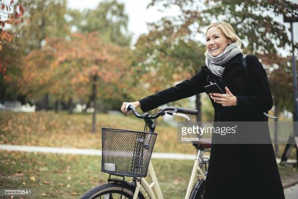 Smiling businesswoman enjoying music while walking with bicycle during autumn